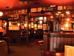 Soft light pub scene with wall decor, bar to the left, and booths to the right